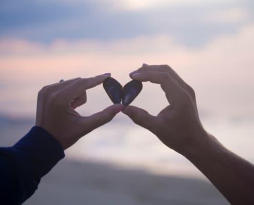 Koronakriisi johti menetyksiin, yhteistyön tiivistymiseen ja oppimiseen. Kuvassa on kaksi kättä, jotka muodostavat simpukankuorilla sydämen.