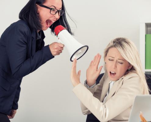 Kuka kuuntelee pomoa blogitekstin kuvassa naisesihenkilö huutaa megafonilla toiselle naisesihenkilölle, joka on kauhuissaan.