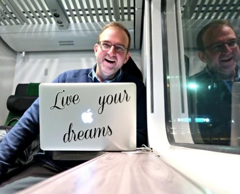 Jan Holmberg junassa kannettavan tietokoneen kanssa. Blogin otsikko on 5 tapaa pilata koulutuksen hyvä esitysmateriaali