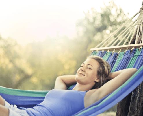 Nainen makaa selällään riippukainussa kesällä. Kuva on Edumarin blogitekstistä: Kesä on kuin tehty palautumista varten.