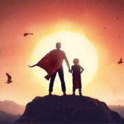 Aikuinen pitää sankarin viitta harteillaan lasta kädestä kiinni ja he katsovat auringonlaskuun. Kuva on osa Edumar Oy:n blogitekstiä: Kuka on elämäsi suurin sankari?