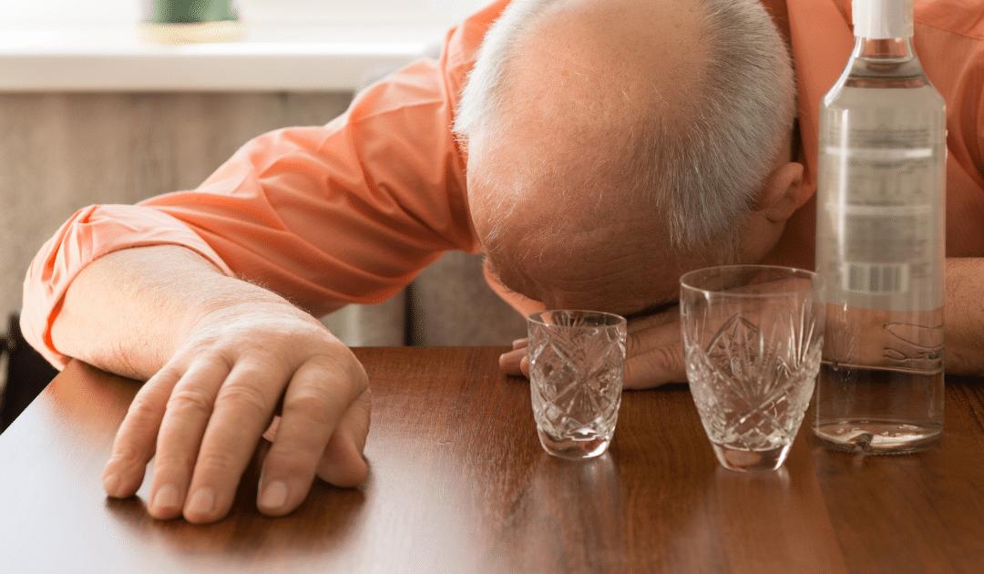 Kuvassa on ikääntynyt mies pää pöydän pintaa vasten ja puupöydällä on alkoholipullo ja kaksi tyhjää lasia. Kuva kuuluu Edumarin blogitekstiin otsikolla: Ikääntyneet ja alkoholi – maksuton verkkokoulutus kiinnostaa